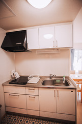 Kitchenette filled with plates, saucepans, cultery etc.