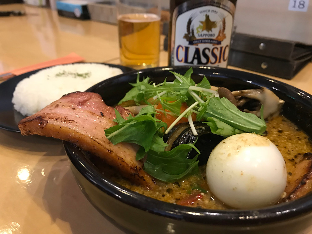 Soup curry with thick sliced bacon, egg, rice and a beer.
