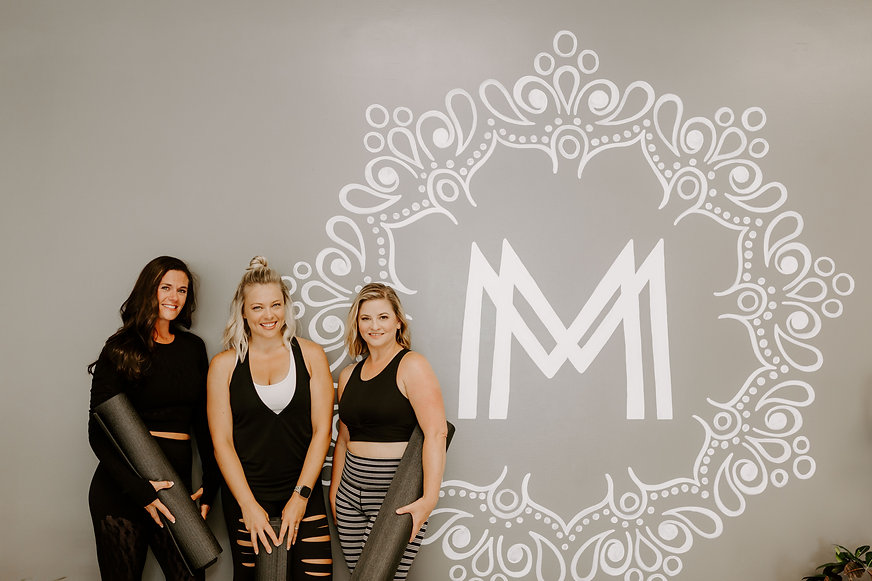 Moxie Fitness team on logo wall