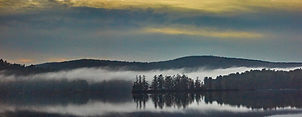 Fog forms over Kezar Lake New Hampshire. Photograph by Ken Schuster.