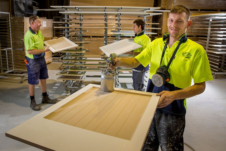 A Castle job seeker in his high-vis work uniform, working in a timber workshop with two colleagues