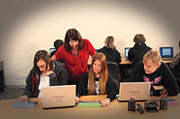 3 young students working at a desk, supported by a Castle employment support manager