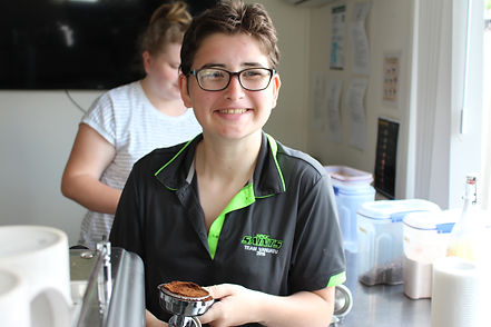 A young female NDIS participant, learning new skills, gaining barista experience