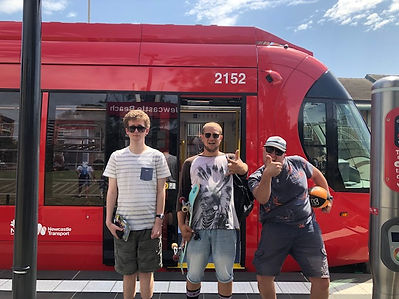 Three teenage mates on a day trip, giving a thumbs up in front of the Newcastle light rail