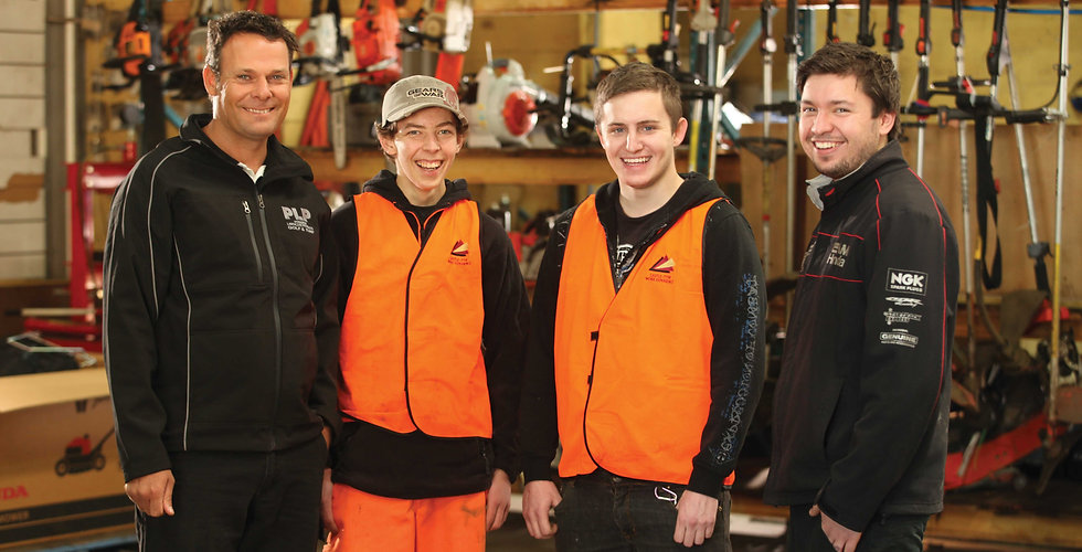 Two Castle job seekers in high visibility vests in a work shop, with their employer and a Castle employment support manager