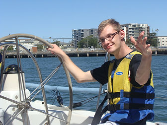 A young male NDIS participant on a day trip, holding the wheel of a boat on Newcasle harbour