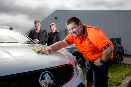 A young male Castle DES participant smiling with two Castle support staff, showcasing his automotive maintenance skills.