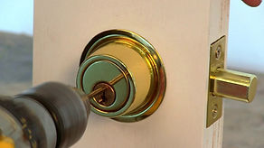 Man drilling deadbolt lock