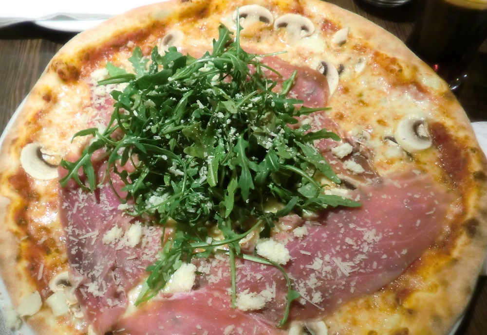 Pizza: mit Parmaschinken, Chamipgnons, Rucola und Grana Padano