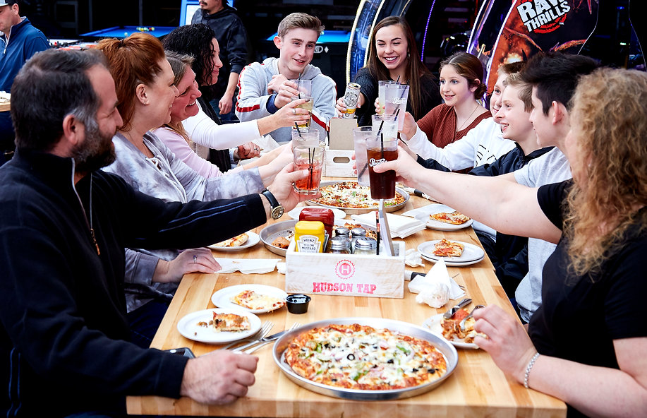 A group of people sitting around a table filled with food and they are cheering with their drinks in hand.