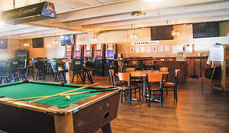Pool table, tables and chairs for dining and slot machines along the wall
