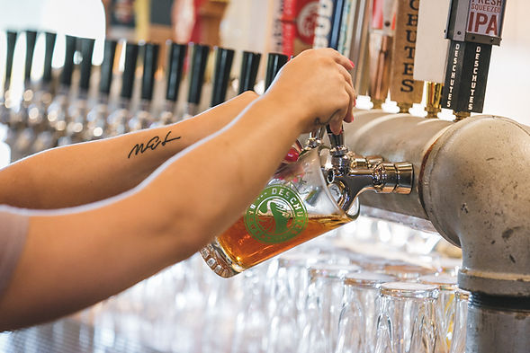 Bartender arms holding a beer glass while filling it up from a beer tap