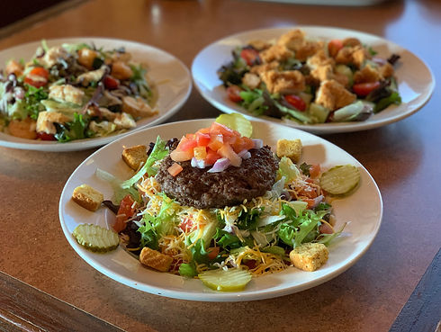 Our Lucy Salad in the front with our Crispy Chicken Salad and Land & Sea Salad in the background