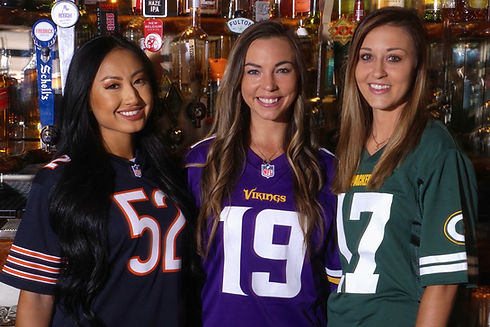 3 girls wearing football jerseys from the Bears, Vikings And Packers.