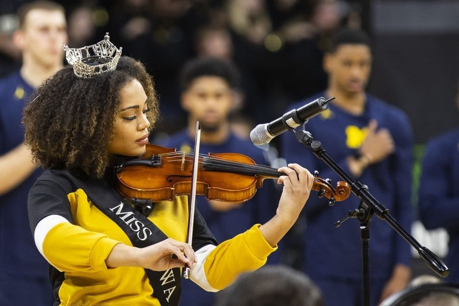 Mikhayla is wearing her crown and intently playing a the Star-Spangled Banner on the violin at a sporting event