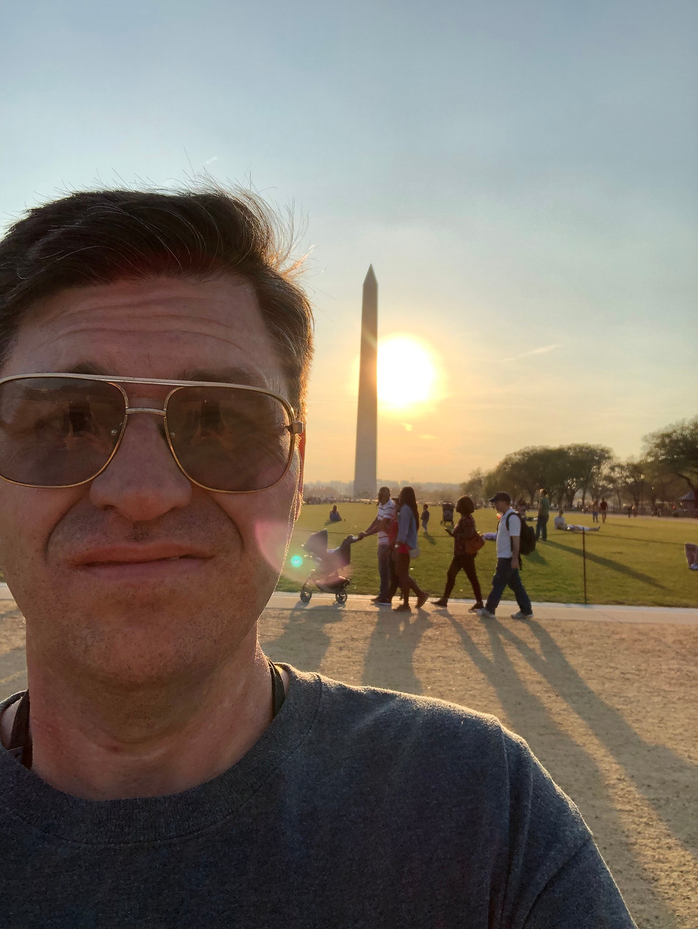Selfie of Mike, wearing aviators with the Washington Monument and the sun setting behind him