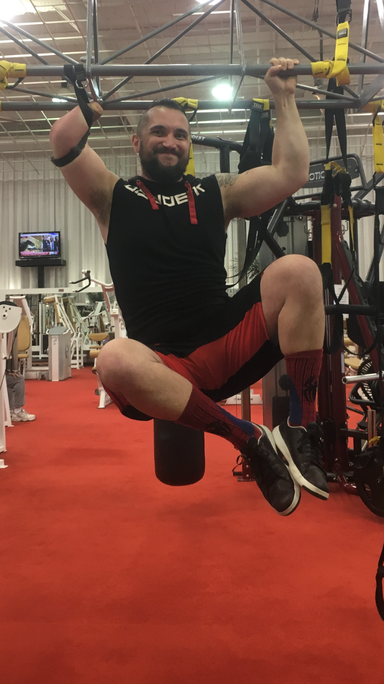 Kevin Herbert is engaging in a pull up, right forearm is using a strap and left hand is holding onto the bar.. Kness and feet are up in a crunch.