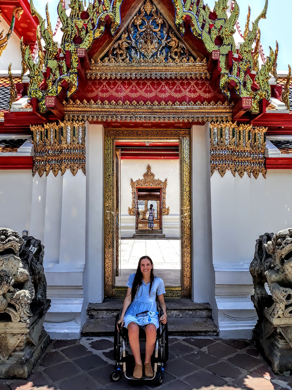 Kendra smiling wide and sitting in her wheelchair in front of a very fancy temple in Thailand