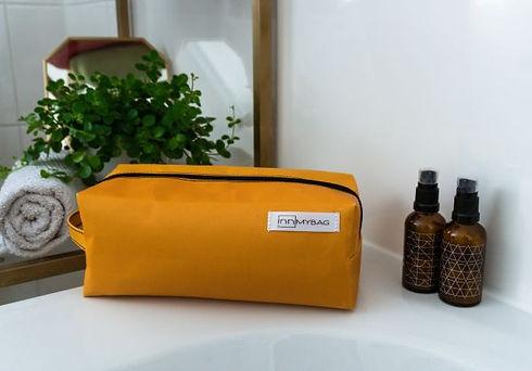 ein orangener INN.MYBAG Kulturbeutel steht in einem Badezimmer vor einer Pflanze