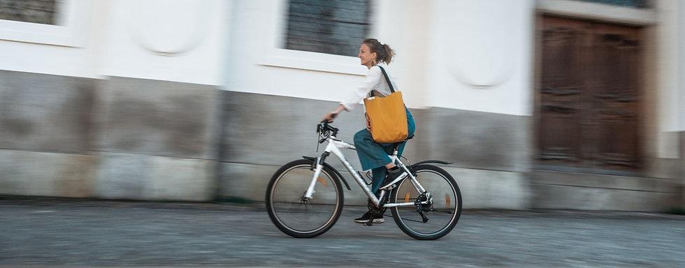 ein mädchen fährt auf einem Fahrrad und hat eine gelbe Tasche auf der Schulter