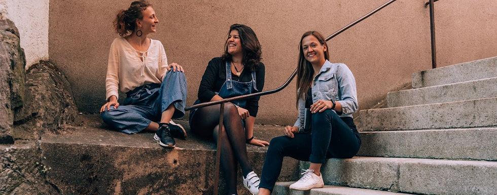 drei mädchen sitzen im Freien und unterhalten sich