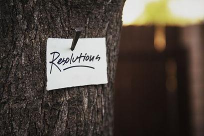 ein zettel mit der aufschrift resolutions hängt an einem Baum