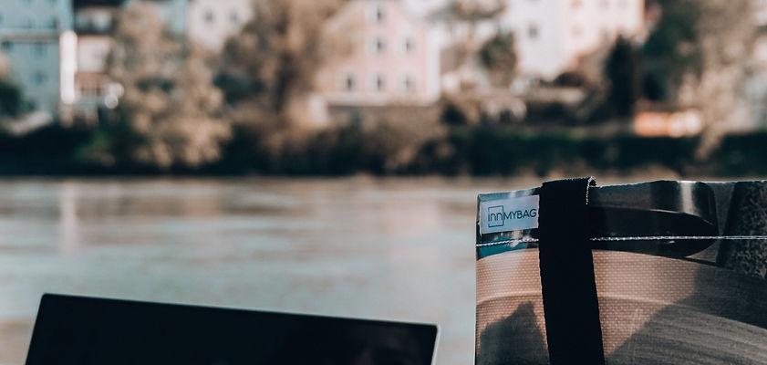 im Vordergrund sieht man den Rand einer Tasche, im Hintergrund ist verschwommen ein Fluss zu erkennen