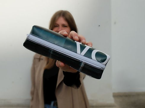 ein Mädchen hält ein Stifte-Mäppchen in die Kamera