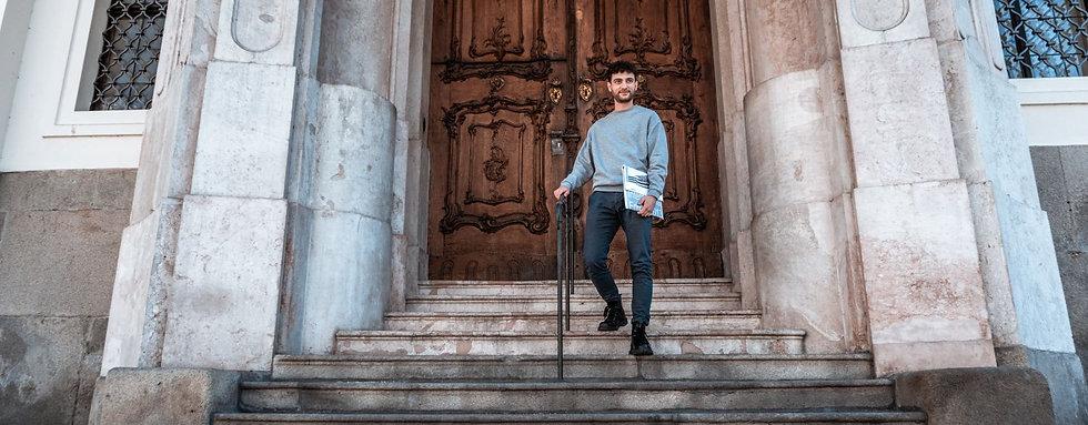 ein mann steht auf einer Treppe und hat einen Laptop in der Hand