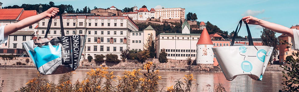 INN.MYBAG Shopper werden hochgehalten. Im Hintergrund ist die Stadt Passau zu sehen