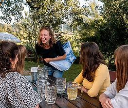 Junge Frauen sitzen im Biergarten. Eine trägt einen INN.Mybag Shopper über der Schulter in den Farben Blau und Weiß