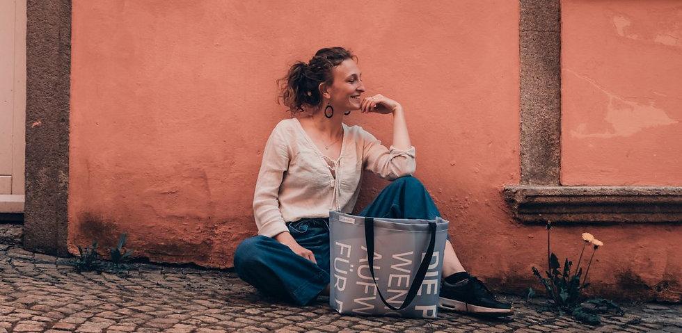 ein lächelndes Mädchen sitzt vor einer roten Wand. Vor ihr steht eine INN.MYBAG Tasche,