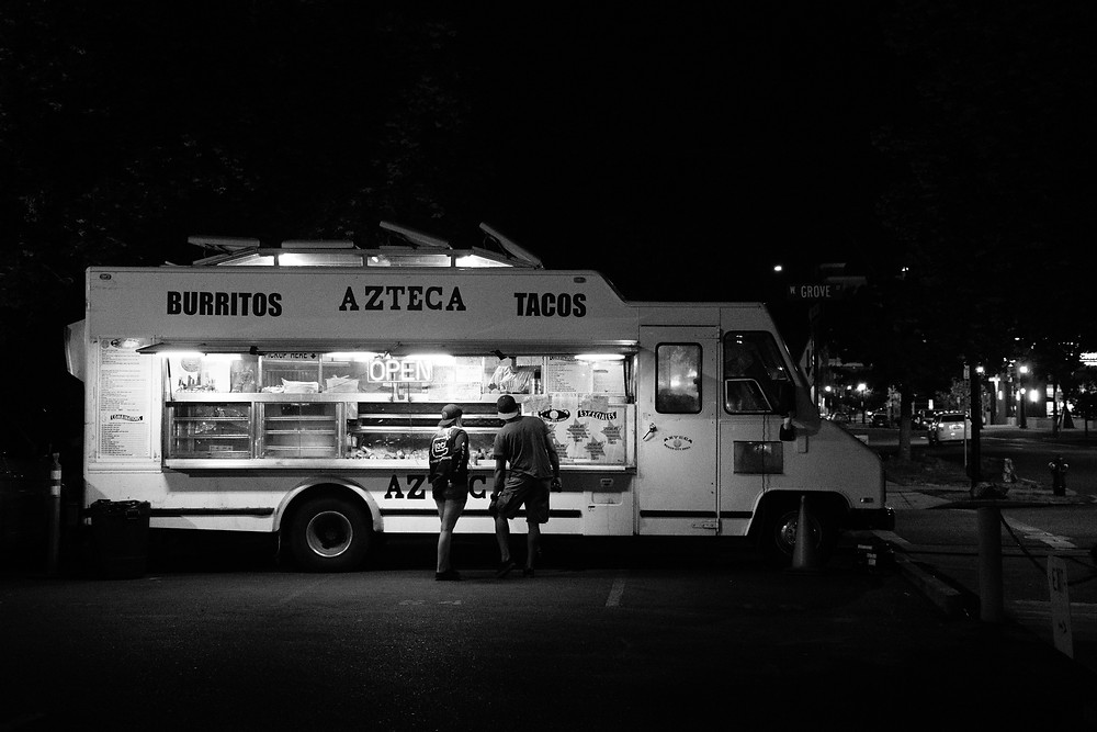 Taco truck with two people standing in front of the order window