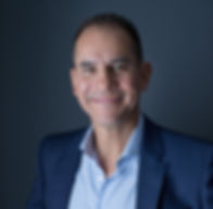 Lithium Battery Expert Dr. Tom Barrera smiling and posing in a suit formal headshot.