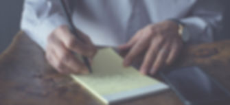 businessman at desk writing on a notepad