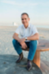 Battery Expert Dr. Tom Barrera sitting on the beach smiling.