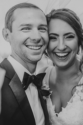Couple smiles at camera on wedding day, bride and groom in tuxedo and wedding dress with big smiles.