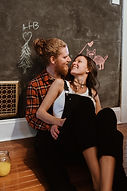 Couple smiles in front of a chalkboard wall for lifestle photography session, couple embraces. Brunette woman in black overalls and white blonde man with red flannel