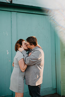 White couple embracing infront of a blue building in pale blue outfits for couples engagement portraits