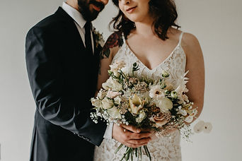 Bride and groom holding white boquet on Elopement wedding day