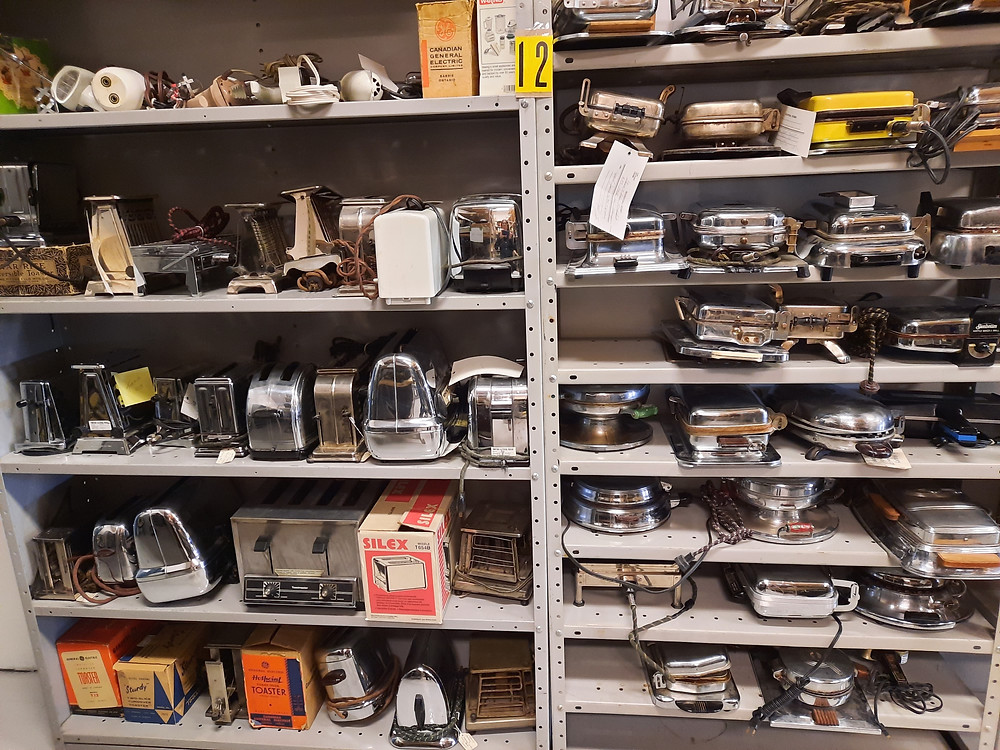 Two shelving units full of old toasters and waffle irons from the Manitoba Electrical Museum's collection.