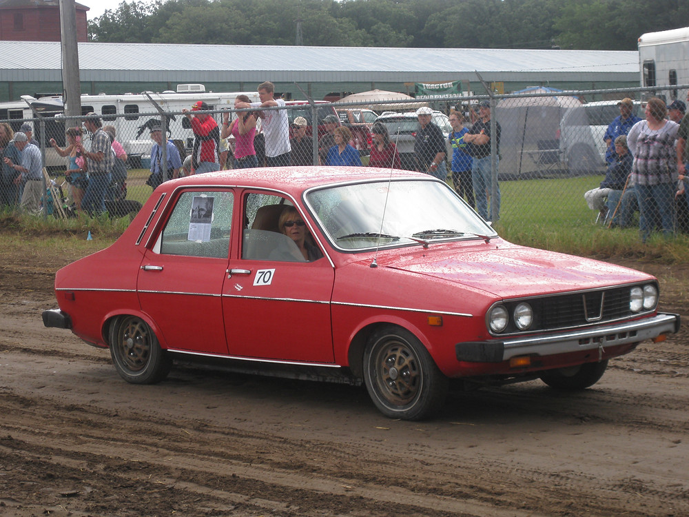 A red 1976 Renault electric car on a dirt road