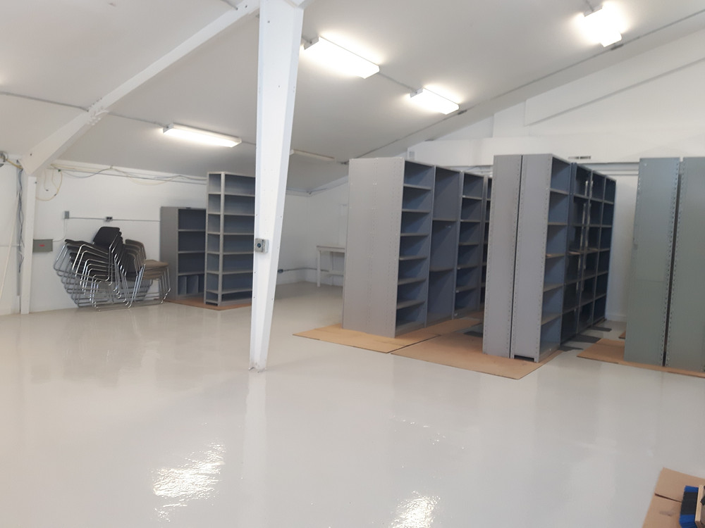A room with a slanted roof, empty except for shelves and a stack of chairs.