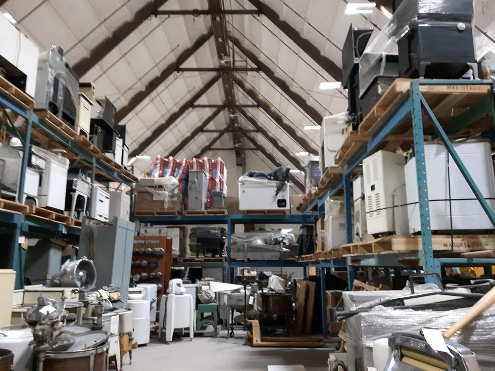 A warehouse with a peaked roof, full of shelves with appliances from the Manitoba Electrical Museum's collection.