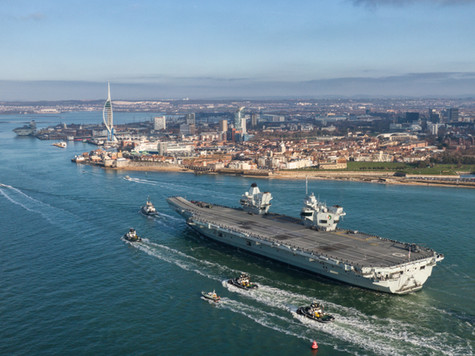 Aircraft Carrier from the Royal Navy aerial drone shot entering portsmouth