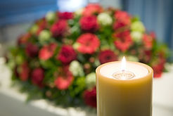 A lit candle in front of a coffin casket at a funeral