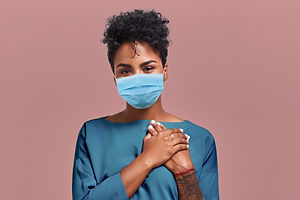 Portrait of kind hearted African American female paramedic wearing a respiratory mask from