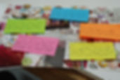 Image: Note cards of multiple colors, layed out over a magazine