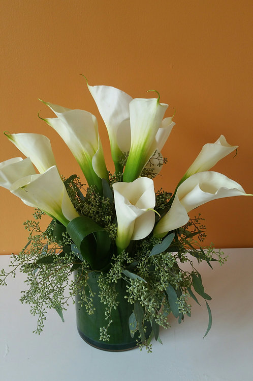 Calla lilies and eucalytus in clear vase