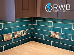 RWB Electrical Services electric sockets fitted on green tiles in kitchen